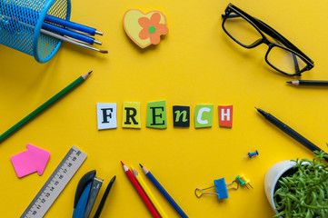 FRENCH - word made with carved letters on yellow desk with office or school supplies, stationery. Concept of Franch language courses