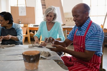Senior friends making clay products