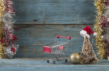 Shopping cart and blank sign over wooden background