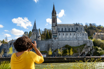 woman photographs the cathedral in Lourdes, France