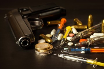 Sales of narcotics. Weapon and drugs on the table. Handgun and ammunition.