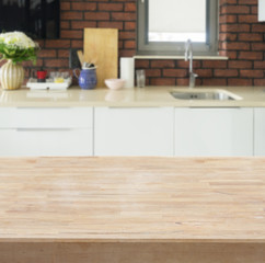 Empty kitchen wooden table top with white modern kitchen in background