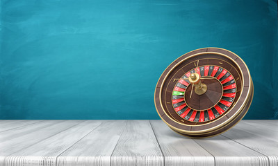 3d rendering of a casino roulette stands on its side on a wooden desk in front of a blue background.