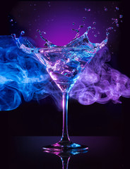martini cocktail splashing on smoky blue and purple background