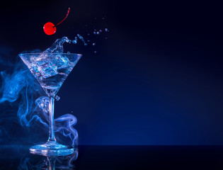 cherry falling into martini cocktail splashing in blue smoky background
