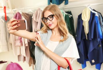 Young woman taking selfie in modern shop
