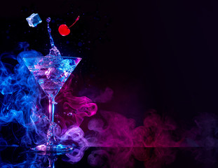 martini cocktail splashing in blue and purple smoky background