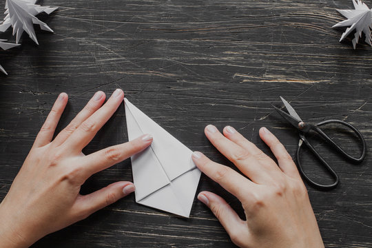 Hands making origami tree