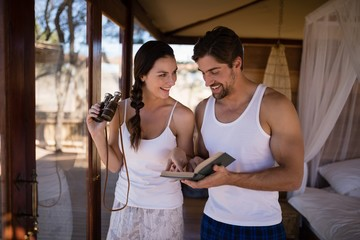 Couple holding binoculars while reading novel during safari