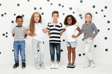 Cute stylish children near light wall