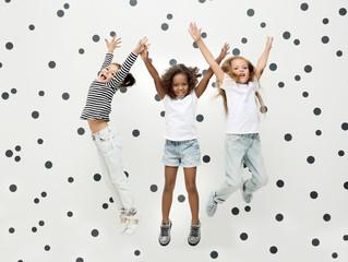 Cute stylish girls jumping indoors