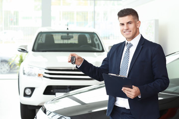 Salesman with key in car salon