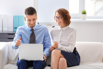 Young man and woman sitting on sofa in office