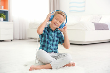 Cute little boy listening to music at home