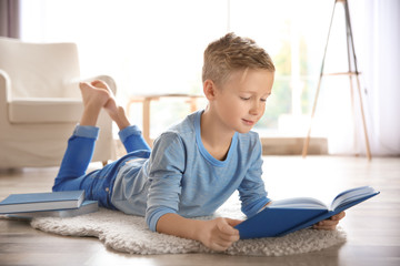 Cute little boy reading on floor at home