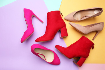 Various female stylish shoes on color background