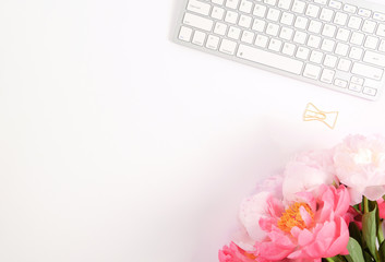 Feminine scene - workplace with keyboard and peonies, flat lay