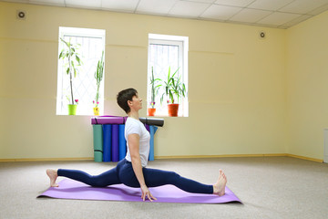 Woman of European appearance engaged in yoga in fitness studio.
