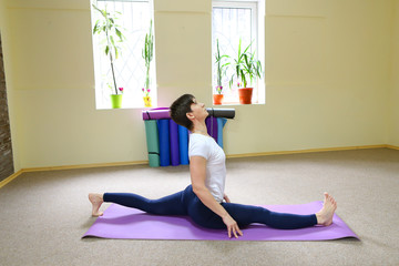 Beautiful young woman with dark haired performs yoga exercises.
