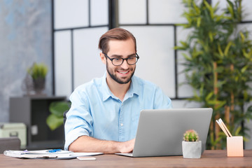Young man using laptop in office