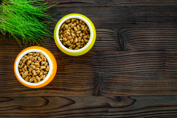 Dry pet food in bowls and green grass in pot on dark wooden background top view copyspace