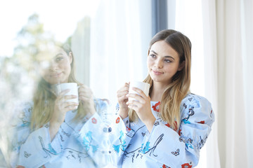 Smiling young woman having her morning tea at home