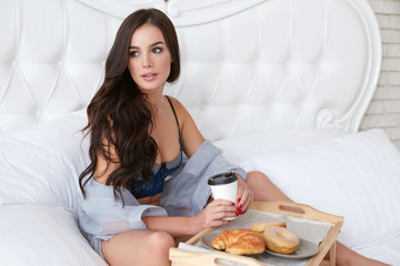 Beautiful brunette women with long hair having breakfast at home sitting in bed. Young girl drinking coffee and eating donuts. Sexy model in lingerie.