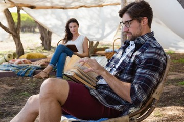 Young couple reading books outside tent