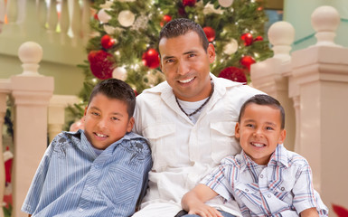 Hispanic Young Father and Sons In Front of Decorated Christmas Tree.