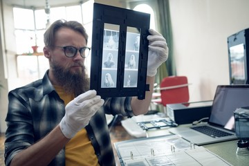 Photographer looking at negatives in frame