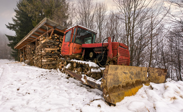 red dozer in snow near the wood shed. lovely rural scenery in forest