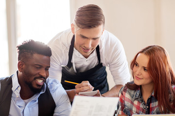 waiter and couple with menu at restaurant