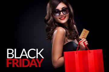 Shopping woman holding grey bag on dark background in black friday holiday