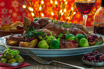 Festive roast duck on wooden table with brussel sprouts, baked potatoes, apples and cranberry sauce