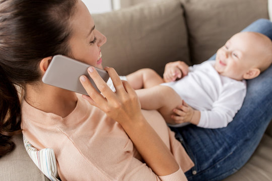 mother with baby calling on smartphone at home