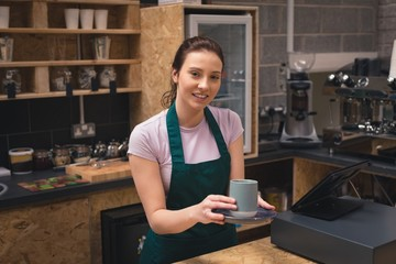 Beautiful waitress holding coffee cup in café