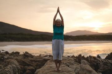 Senior woman doing yoga on seaside rocks