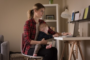 Young woman using laptop computer while sitting with son
