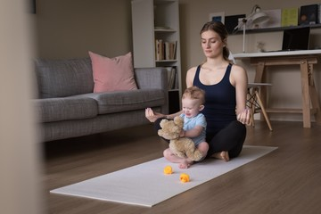 Boy standing by woman meditating at home