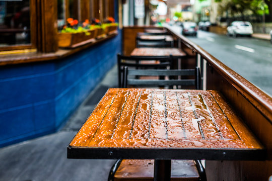 Wet tables closeup outside restaurant during heavy rain with street and cars