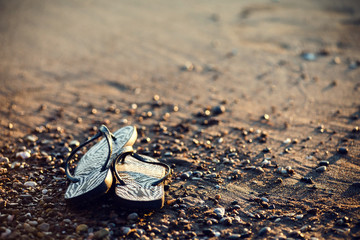 Summer vacation concept. Two sandals on the sandy tropical beach