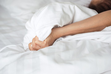 Hands of lovers having sex on a bed in morning with lust and love