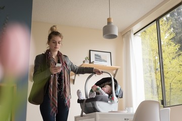 Woman using phone while holding baby in stroller at home