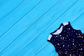 Pretty baby dress and copy space. Casual little lady outfit on blue wooden background. Clothing for small girl.