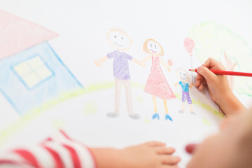 Cute child draws house and family on paper