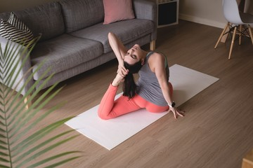 High angle view of young woman doing one-legged king pigeon pose