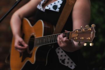 Closeup of a woman's hands playing guitar