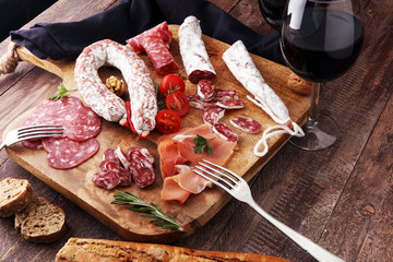 Wooden cutting board with prosciutto, salami, sausages, wine, bread  and  rosemary