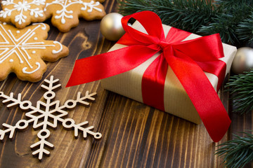 Christmas gift and cookies on the wooden background