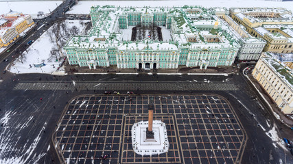 Aerial front view at the Winter Palace building, exterior with snow Palace Square and Aleksandr Column at winter season. Top view. Saint-Petersburg, Russia
